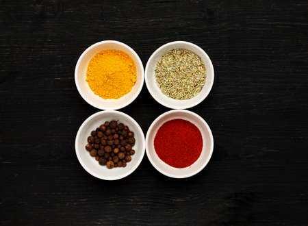 Different spices in ceramic bowls on a black wooden table, top view 写真素材