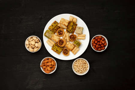 Traditional oriental sweets in white plate with different nuts on a black table, top view