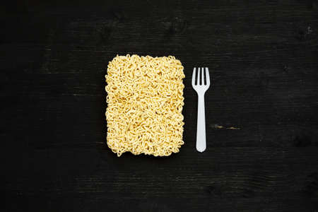 Briquet of instant noodles with plastic fork on a black wooden table, top view 写真素材