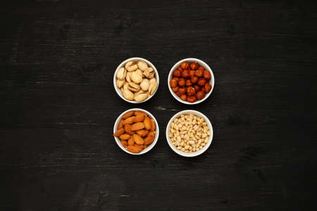 Different nuts in ceramic bowls on a black wooden table, top viev