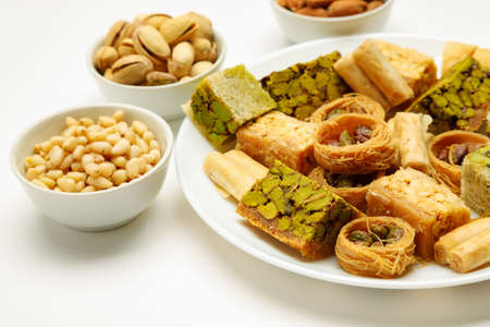 Traditional oriental sweets in white plate with different nuts on a white table, side view