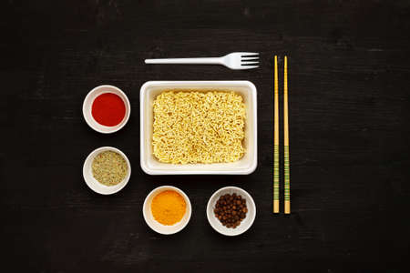 Instant noodles in container with plastic fork, chopsticks and spices on a black wooden table, top view