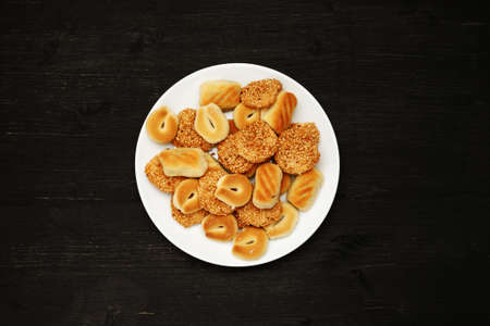 Traditional oriental cookies with sesame on a black table, top view 写真素材