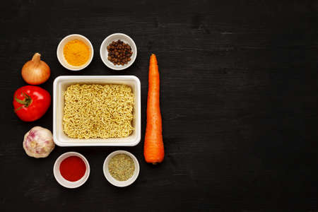 Instant noodles in contaiber with vegetables and spices on a black wooden table, top view, text space 写真素材