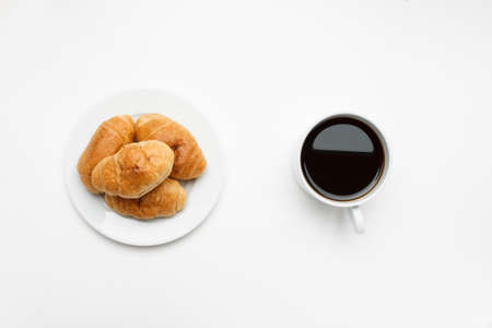 Fresh croissant in a white plate and cup of coffee, top view 写真素材