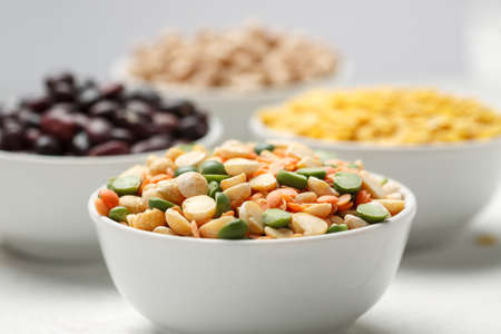 Different beans in bowls on a white wooden table