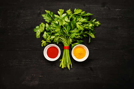 Bunch of green fresh parsley with spices in white ceramic bowls on a black wooden table, top view