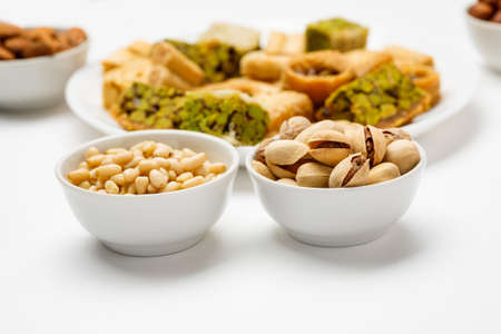 Pine nut and pistachio in ceramic bowls with traditional oriental sweets in the background 写真素材 - 126219645