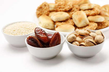 Dried dates, sesame and pistachio in white ceramic bowls with traditional oriental cookies in the background, close-up shot
