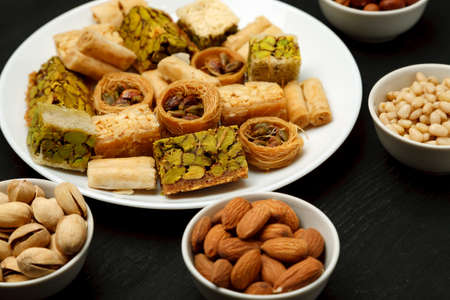 Traditional oriental sweets in white plate with different nuts on a black table, close-up shot