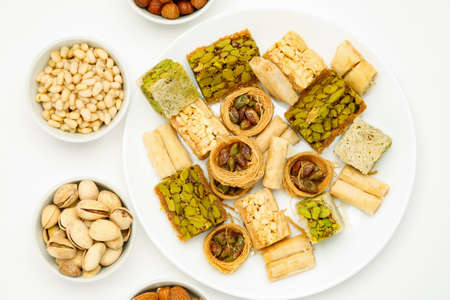 Traditional oriental sweets in white plate with different nuts on a white table, top view