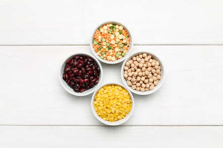 Different beans in bowls on a white wooden table, top view