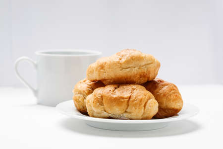Fresh croissant in a white plate and coffee mug on a white table 写真素材 - 126219709
