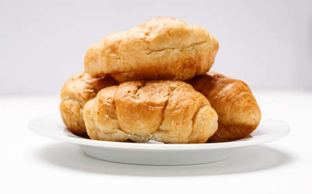 Fresh croissant in a white plate on a white table 写真素材