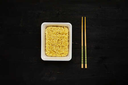 Instant noodles in container with chopsticks on a black wooden table, top view 写真素材