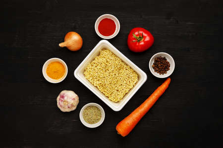 Instant noodles in contaiber with vegetables and spices on a black wooden table, top view 写真素材 - 126219771