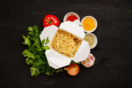 Dry noodles in paper box with greenery, vegetables and spices on a black table, top view