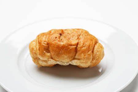 Single fresh croissant in a white plate on a white table 写真素材 - 126219780