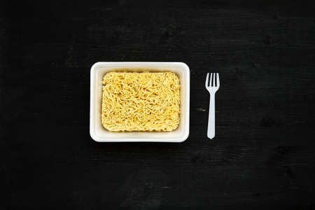 Instant noodles in container with plastic fork on a black wooden table, top view