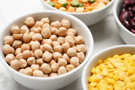 Chickpea and other beans in white bowls on a wooden table 写真素材