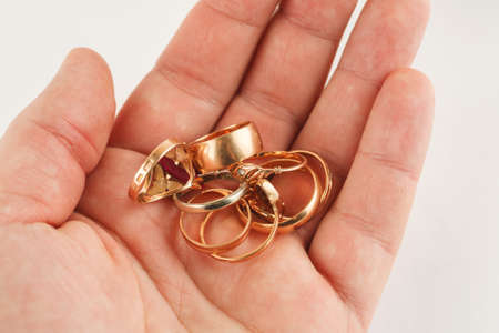 Pile of gold jewellery in hand, closeup shot