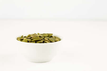 Peeled green pumpkin seeds in a white bowl