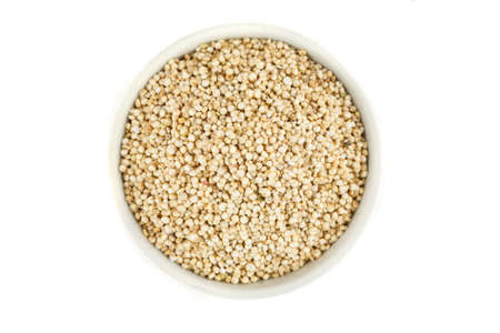 Quinoa raw seeds in white ceramic bowl on a white, top view