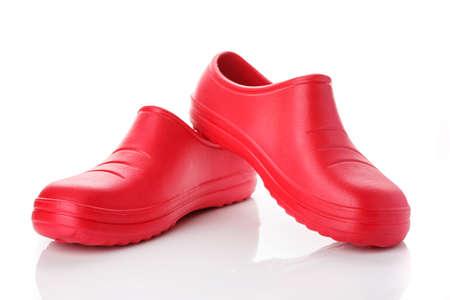 Pair of red rubber shoes on a white background