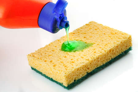Yellow sponge with bottle pouring cleaning liquid 写真素材
