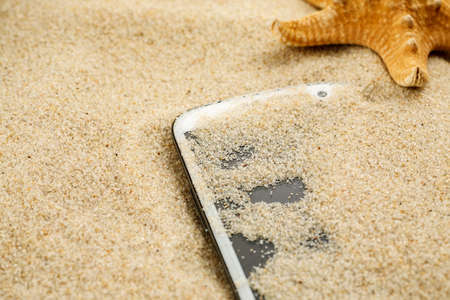 White smartphone lost in sand on the beach 写真素材 - 126219929