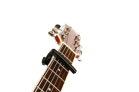Acoustic guitar neck with capo on a white background