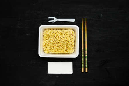 Instant noodles in container with plastic fork, chopsticks and napkin on a black wooden table, top view