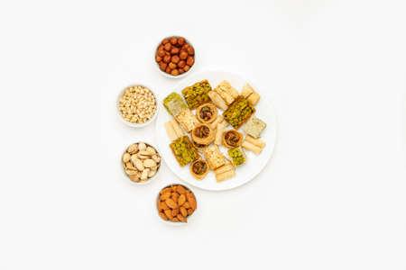 Dulces orientales tradicionales en plato blanco con diferentes frutos secos sobre una mesa blanca, vista superior