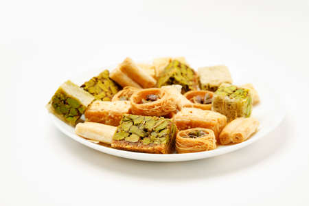 Traditional oriental sweets in white plate with different nuts on a white table, side view 写真素材 - 128951695