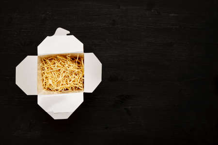Dry noodles in paper box on a black table, top view, text space 写真素材 - 128952728