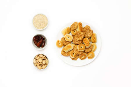 Traditional oriental cookies with sesame, dates and pistachio on a white table, top view Фото со стока