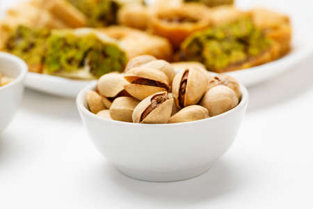 Pistachio in ceramic bowl with traditional oriental sweets in the background, close-up