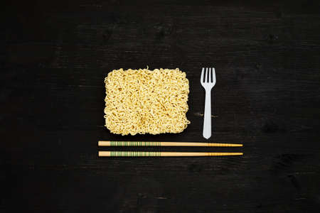 Instant noodles with plastic fork and chopsticks on a black wooden table, top view Фото со стока