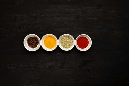 Different spices in ceramic bowls on a black wooden table, top view Фото со стока