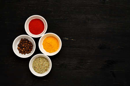 Different spices in ceramic bowls on a black wooden table, top view, text space 写真素材 - 128952453