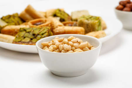Pine nut in ceramic bowl with traditional oriental sweets in the background, close-up Фото со стока