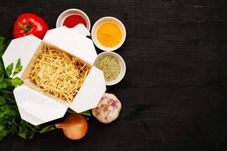 Dry noodles in paper box with greenery, vegetables and spices on a black table, top view, text space