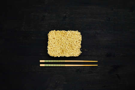 Briquet of instant noodles with chopsticks on a black wooden table, top view Фото со стока