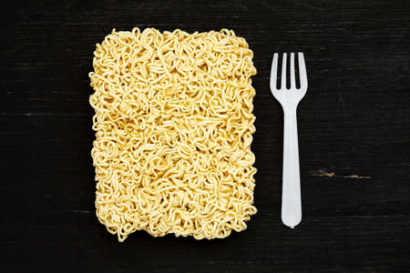 Briquet of instant noodles with plastic fork on a black wooden table, top view Фото со стока