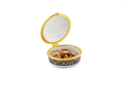Small ceramic box with gold jewelry in it on white background Фото со стока