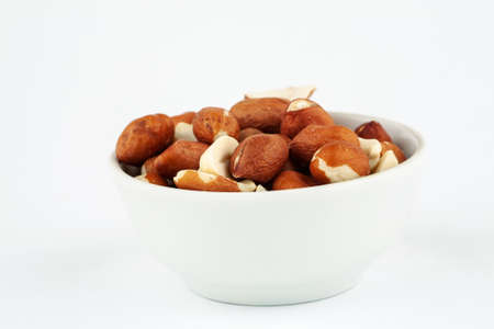 Pile of raw unpeeled peanut in white ceramic bowl on white background
