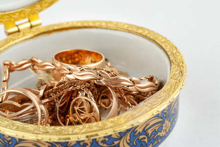 Small ceramic box with gold jewelry in it on white background, macro 写真素材 - 128951998