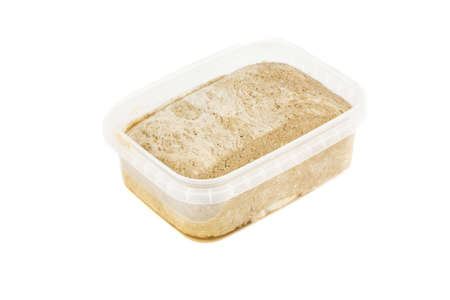 Sunflower halva in plastic container on white background