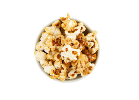 Sweet popcorn in ceramic bowl on white background, top view