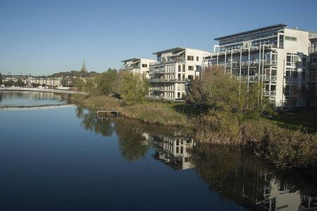 seaports: Withe houses  in Hammarby seaport located on the water with trees and reflection Stock Photo